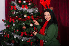 Happy woman decorating Christmas tree Royalty Free Stock Images