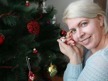 Happy woman decorating a Christmas tree Stock Images