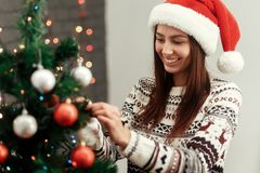 Happy woman decorating christmas tree. wearing sweater reindeers and santa hat smiling on background of lights. joyful moments in. Winter holidays. seasonal royalty free stock photos