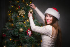 Happy woman decorating a christmas tree Royalty Free Stock Photos