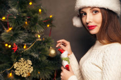 Happy woman decorating a christmas tree Royalty Free Stock Photography