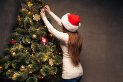 Happy woman decorating a christmas tree Stock Photography