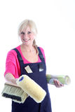 Happy woman decorator. In dungarees holding a roll of wallpaper, brush and roller as she embarks on a redecoration project Royalty Free Stock Photography