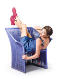 Happy woman in denim dress kicking back on chair Royalty Free Stock Images