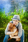Happy woman in denim overalls and hat with her dog Shar Pei sitting in the meadow near the lake at sunset Royalty Free Stock Images