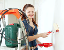 Happy woman in deniums paints wall Royalty Free Stock Image