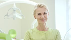 Happy woman dentist standing in dental office. Blonde nurse smiling on camera