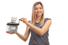 Happy woman destroying a dollar banknote in a paper shredder Stock Photography