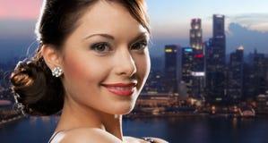 Happy woman with diamond earring over night city Stock Photos