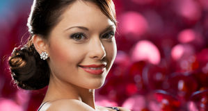 Happy woman with diamond earring over red lights Royalty Free Stock Photo