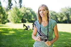 Happy Woman With Digital Camera In Park Stock Photos