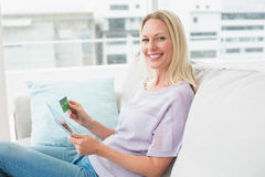 Happy woman with digital tablet and credit card on sofa Royalty Free Stock Image