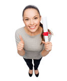 Happy woman with diploma showing thumbs up Royalty Free Stock Images
