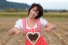 Happy woman in a dirndl pointing to a heart. Happy young German or Bavarian woman in a dirndl pointing to a decorative iced heart shaped biscuit she is wearing stock photo