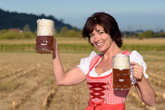 Happy woman in a dirndl toasting with beer. Happy attractive young woman in a traditional Bavarian dirndl toasting with two large glass tankards of cold frothy royalty free stock images