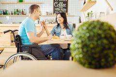 Happy woman and disabled man listening to music. Music. Beautiful inspired dark-haired women and a handsome alert handicapped men sitting at the table in a cafe Royalty Free Stock Image