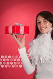 Happy woman displaying a red Christmas gift Royalty Free Stock Photography