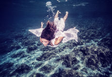 Happy woman diving into the sea Stock Images