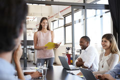 Happy woman with document stands addressing team at meeting Stock Photo