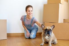 Happy woman with dog and boxes moving to new home. Mortgage, people and real estate concept - happy young woman with dog and boxes moving to new home Stock Photos