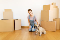 Happy woman with dog and boxes moving to new home. Mortgage, people and real estate concept - happy young woman with dog and boxes moving to new home Stock Image