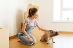 Happy woman with dog and boxes moving to new home Royalty Free Stock Photography
