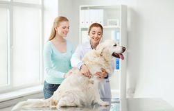Happy woman with dog and doctor at vet clinic Royalty Free Stock Image