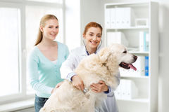 Happy woman with dog and doctor at vet clinic Stock Photo