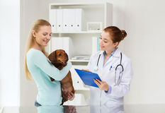 Happy woman with dog and doctor at vet clinic Royalty Free Stock Photography