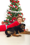 Happy woman with dog lying by Xmas tree Royalty Free Stock Photos