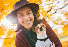 Happy woman with dog outdoors in autumn Stock Photography