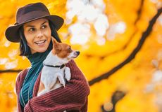 Happy woman with dog outdoors in autumn lookin Royalty Free Stock Photo