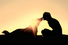 Happy Woman and Dog Outside Silhouette. A silhouette of a happy young woman is sitting outside at sunset lovingly kissing her large German Shepherd mix breed dog Stock Photo