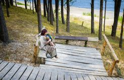 Happy woman with a dog is resting near a beach of the Baltic Sea Stock Photography