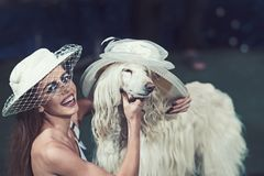 Happy woman and dog in retro hats. Sensual woman smile to funny pet. Fashion girl and domestic animal. Friendship and stock images