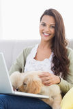 Happy woman with dog using laptop on sofa Stock Photography