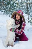 Happy woman with dog in winter forest Stock Photo
