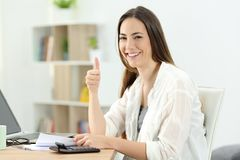 Happy woman doing acoounting looking at you royalty free stock photos
