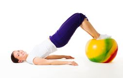 Happy woman doing fitness exercises with ball. Happy young woman doing fitness exercises with ball, isolated on white Royalty Free Stock Photography