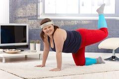 Happy woman doing gymnastics at home royalty free stock photo