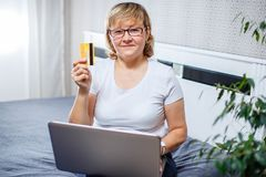 Happy woman doing her shopping online using a credit card. Stock Photography