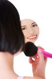 Happy woman doing make up using a mirror Royalty Free Stock Image