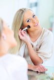 Happy Woman Doing Makeup Stock Images
