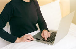 Happy woman doing online shopping at home on bed. Happy woman doing online shopping at home on bed Stock Photos