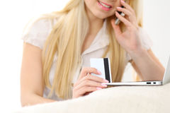 Happy woman doing online shopping at home . Close- up of a hand holding a credit card next to a laptop Royalty Free Stock Photos