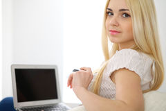 Happy woman doing online shopping at home . Close- up of a hand holding a credit card next to a laptop Stock Photos