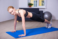 Happy woman doing push up exercise at home. Young happy woman doing push up exercise at home royalty free stock photography