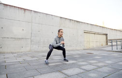 Happy woman doing squats and exercising outdoors Royalty Free Stock Image