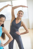 Happy Woman Doing Stretching Exercise With Friend Stock Image