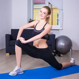 Happy woman doing stretching exercise at home Royalty Free Stock Photos